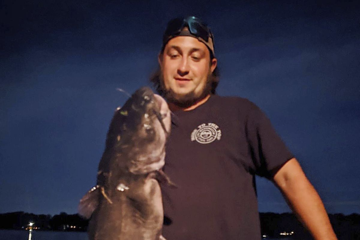 Ben Tomkunas holds a catfish he caught in Coventry, Conn., on Aug. 21, 2021, that has smashed a state record and could also be a world record for the species — though the evidence now has been eaten.