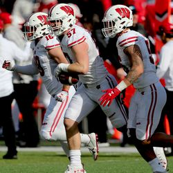 Jack Sanborn (#57) is escorted off the field after his 1st half interception. The Badgers would use the short field to score a quick touchdown.