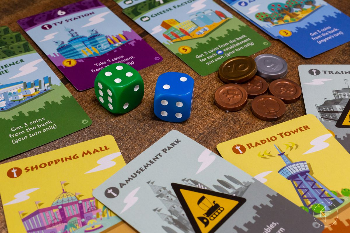 A pile of bits from Machi Koro, including a shopping mall, an amusement park, and a radio tower. Two dice and some coins sit in the center of the frame.
