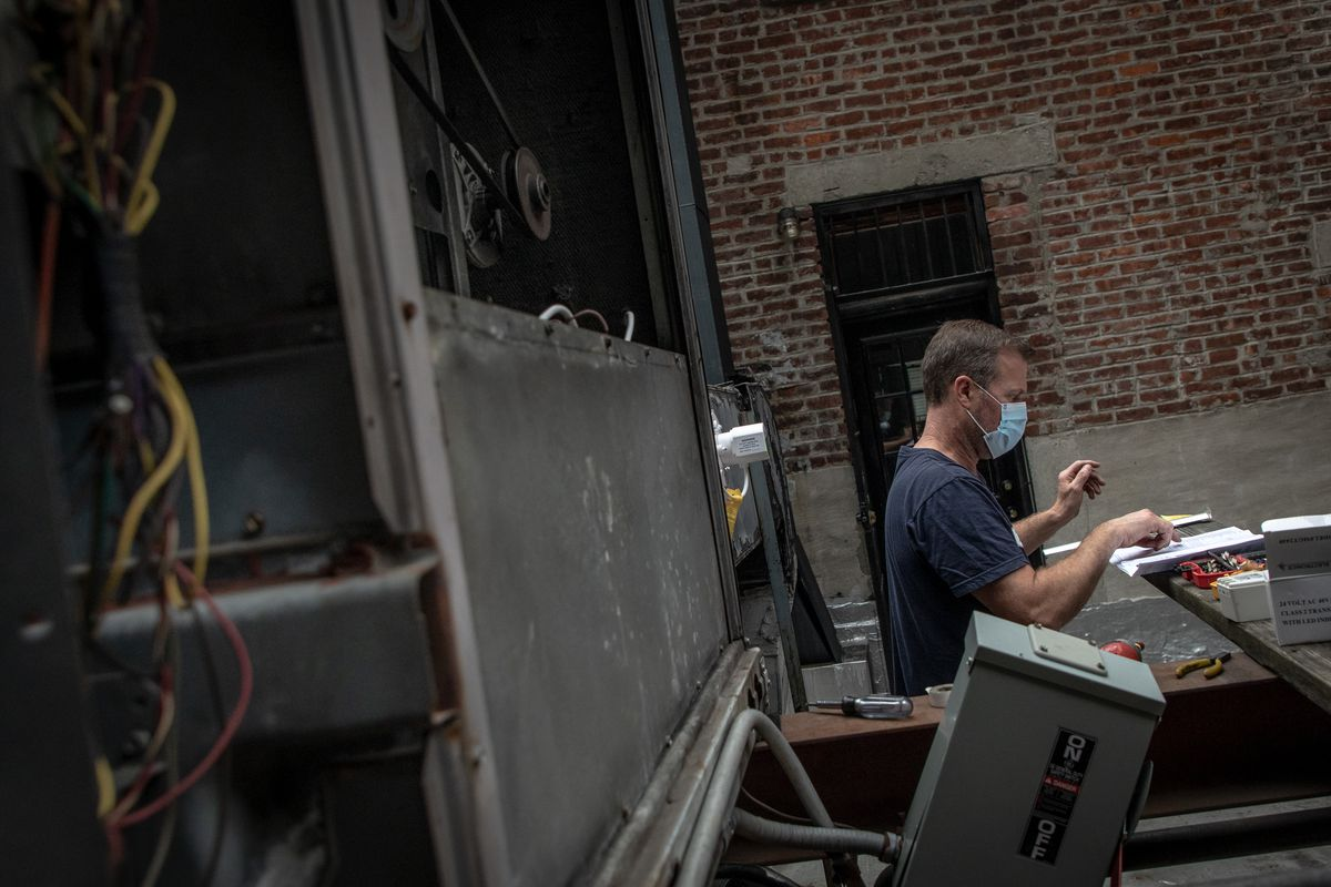 Scott Bankey augments the HVAC unit on the roof of The Musket Room