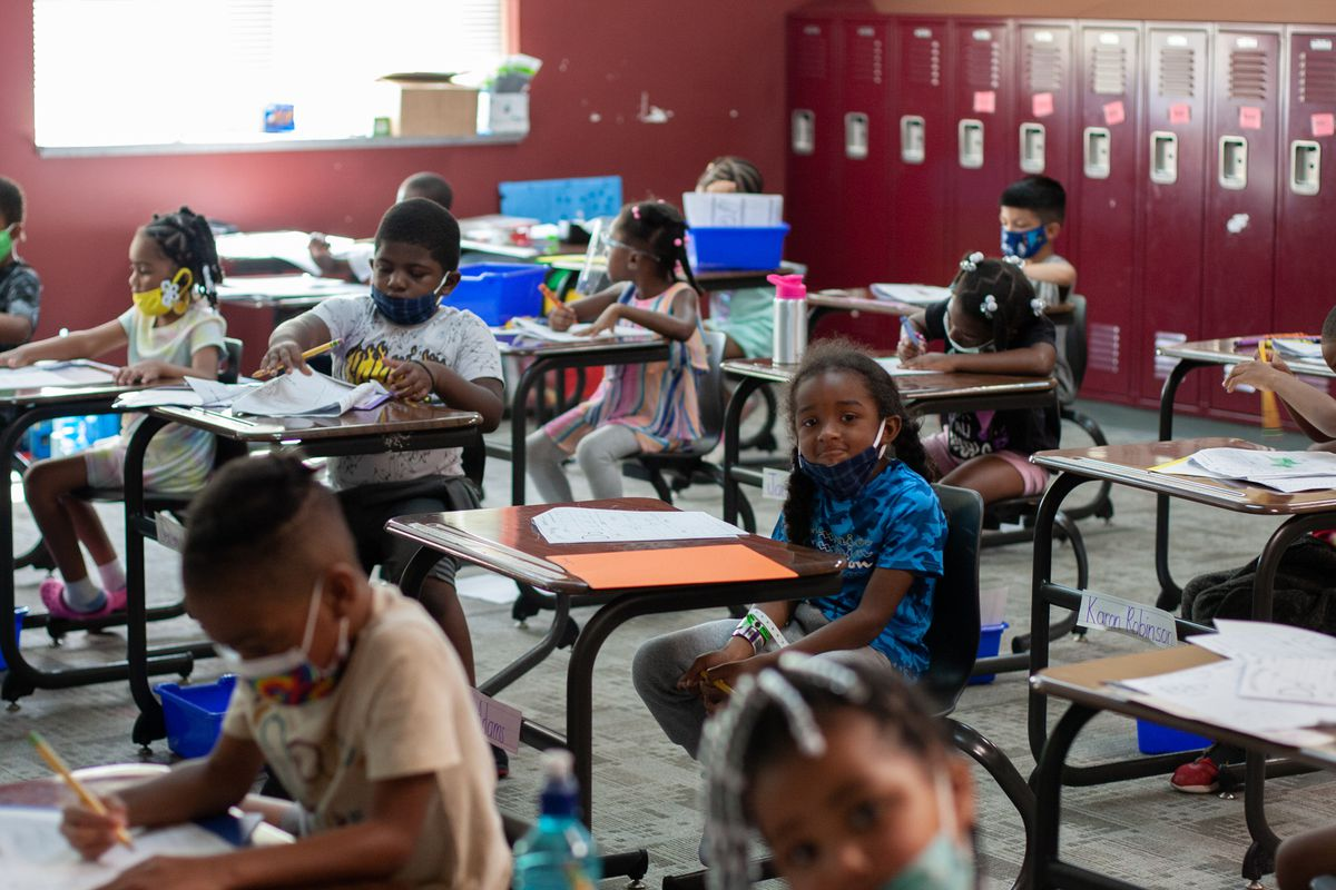 About 10 young kindergarten students sit at small desks looking at worksheets in a classroom lined with red lockers. One girl in a blue shirt and a black face mask in the middle of the photo looks at the camera.