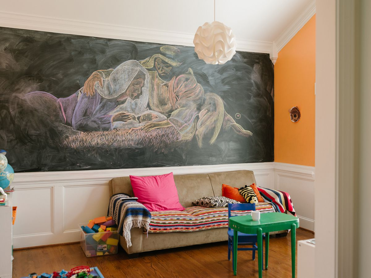 The playroom with a chalkboard wall that has a mural drawn on it.