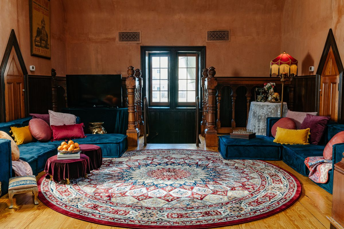 Living room filled with ornate rugs and velvety furniture in blue, red, yellow, and purple.