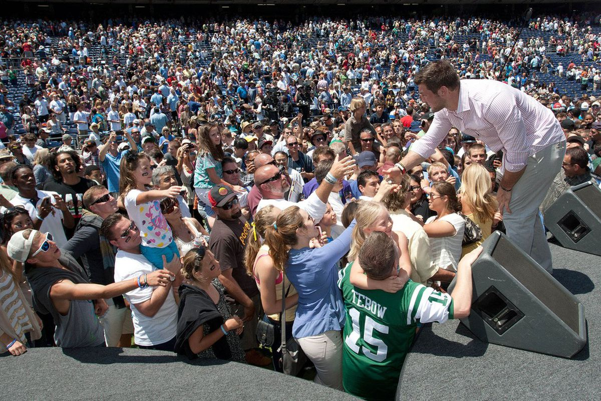 June 17, 2012; San Diego, CA, USA; New York Jets quarterback Tim Tebow shakes hands with fans after speaking to a crowd during a Father's Day service at Qualcomm Stadium. Jake Roth-US PRESSWIRE