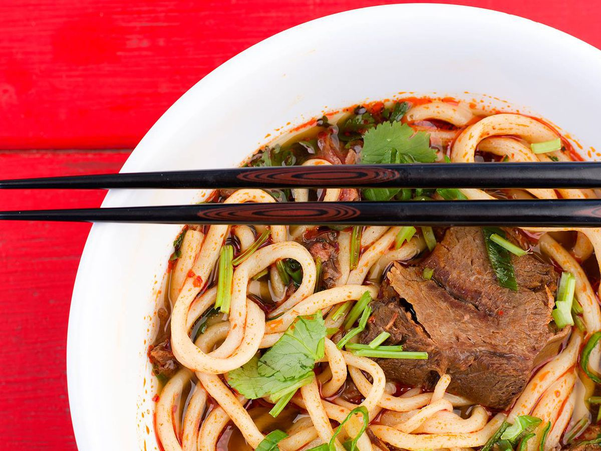 Noodles served in a red broth inside a white bowl. The bowl is placed on a red background.