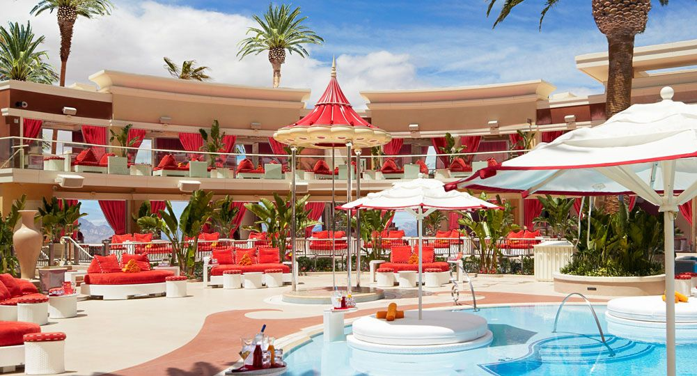 Pool with red umbrellas and daybeds