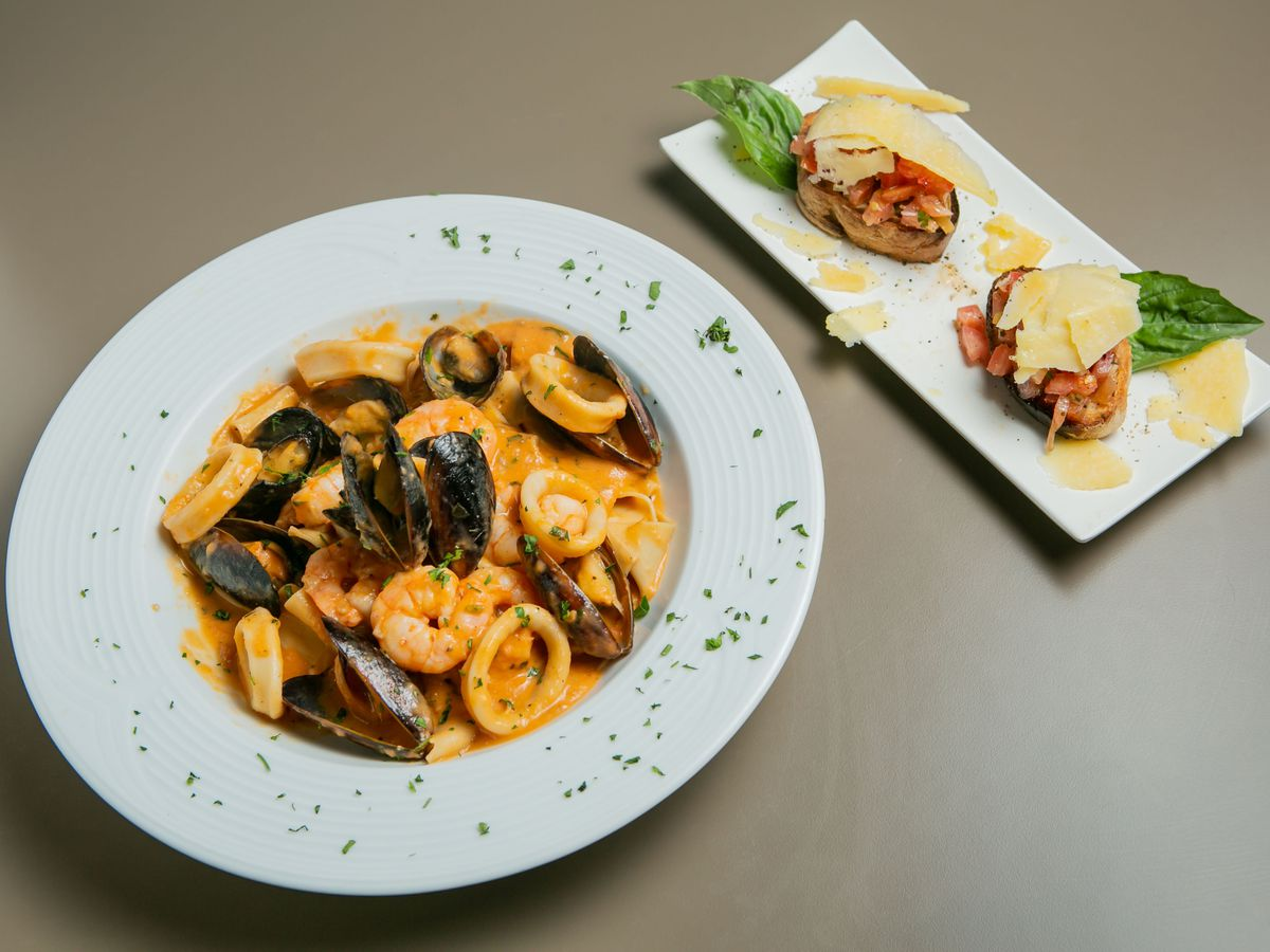 A bowl of shellfish next to a rectangular plate with two bruschetta.
