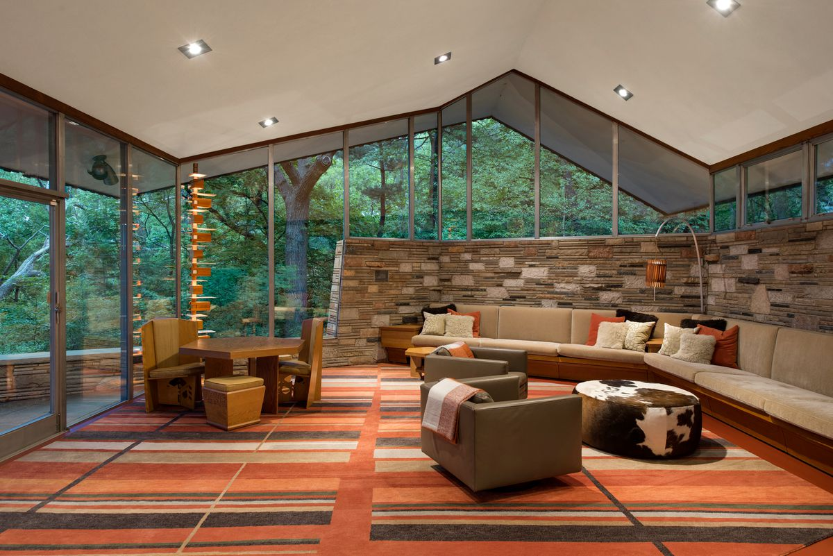 Striped orange and red carpet in a living room contrasts with a built-in bench and other furniture.