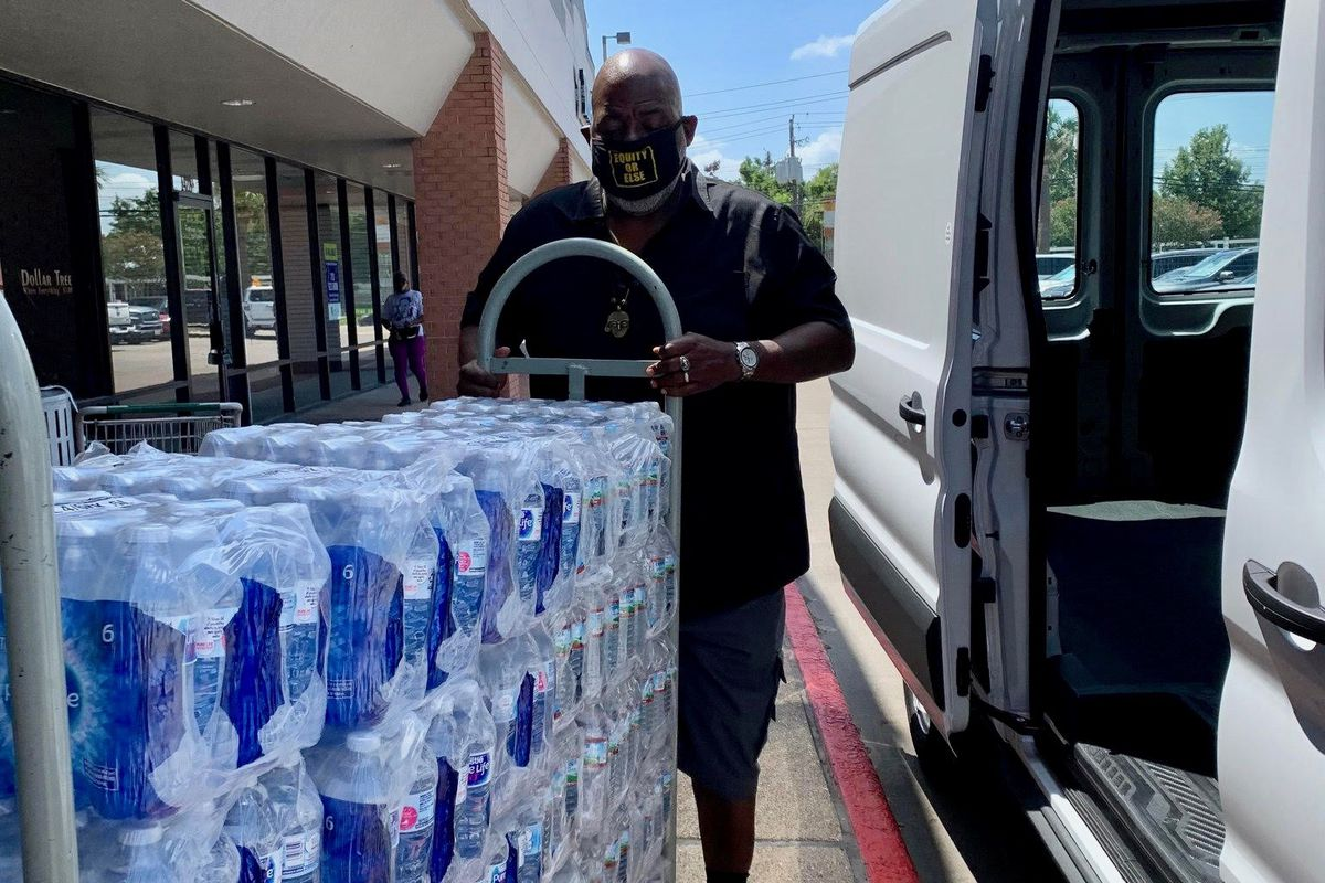 J4J National Director Jitu Brown loads water driven to Hurricane Ida victims for pick-up in Baton Rouge.