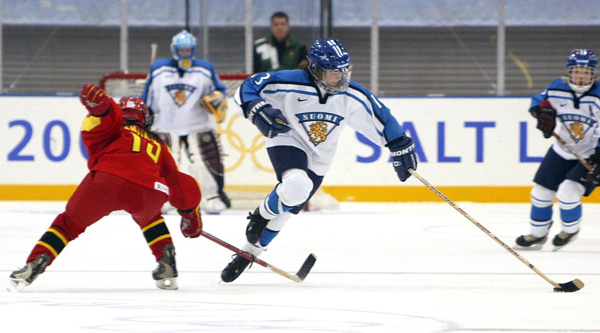 Riikka Nieminen (c) of Finland heads down ice as J
