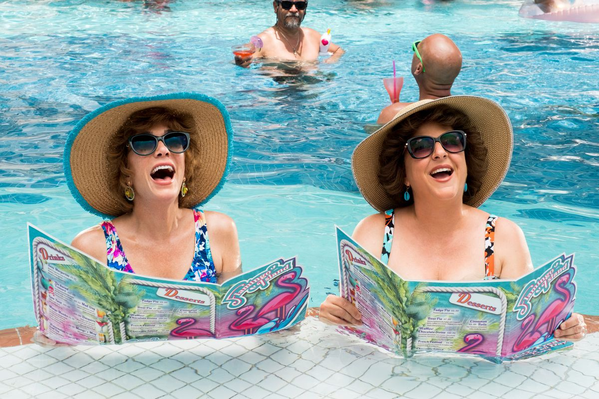 Two middle-aged white women in a pool wearing shades and hats.
