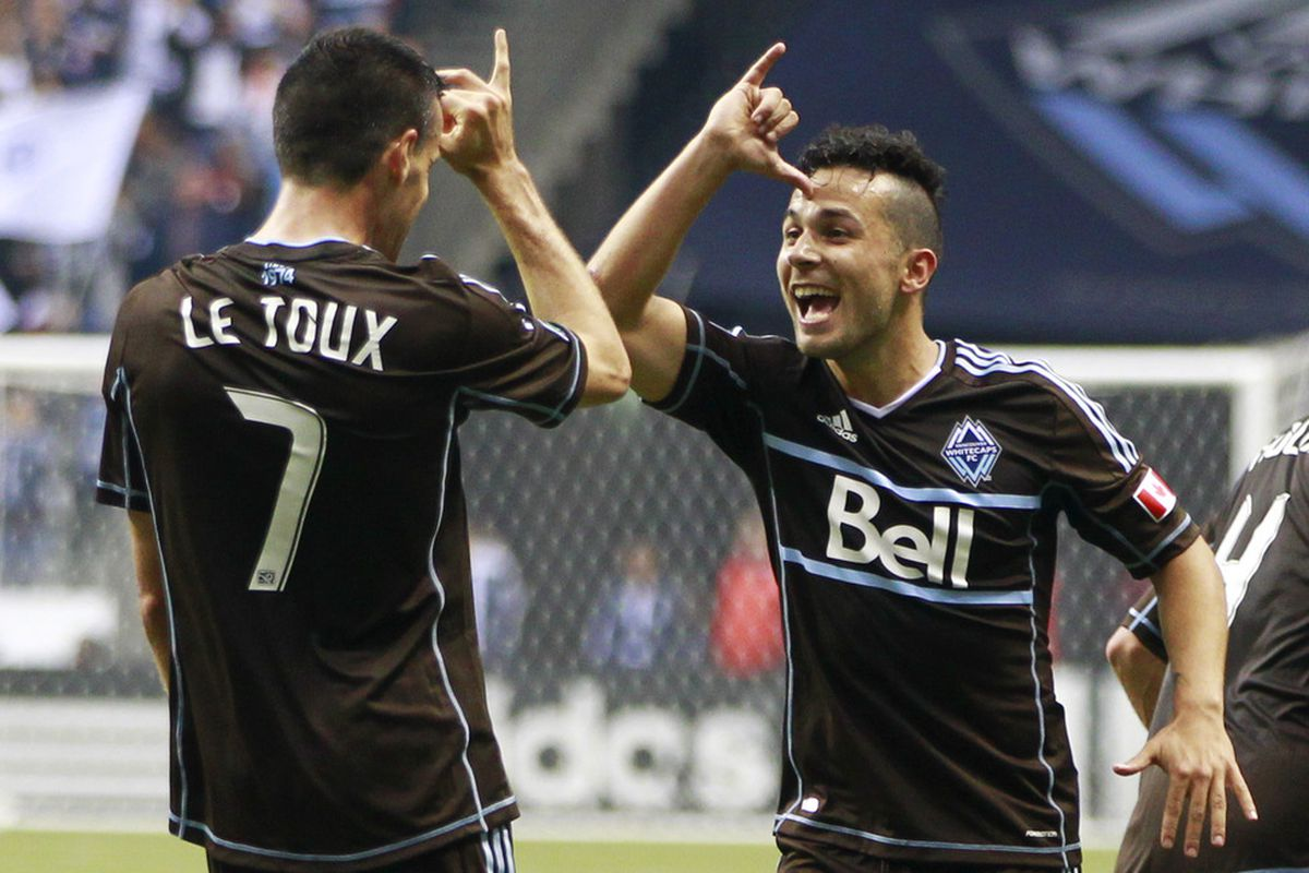 Sebastien Le Toux #7 celebrates his goal with teammate and setup man Davide Chiumiento #20 of the Vancouver Whitecaps during their match against the Colorado Rapids at BC Place June 16. Vancouver won 1-0. (Photo by Jeff Vinnick/Getty Images)