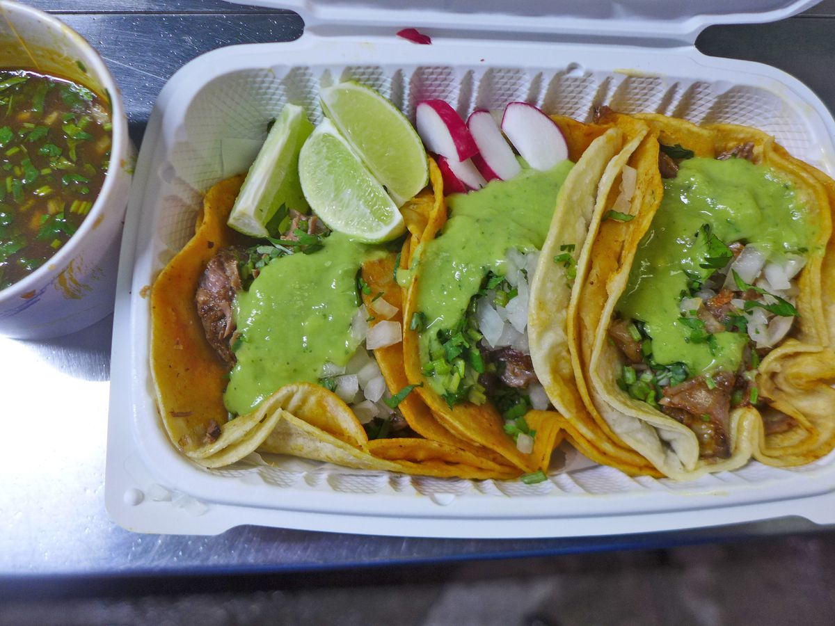 Three small meat tacos in a white plastic tray with a dark soup on the side.