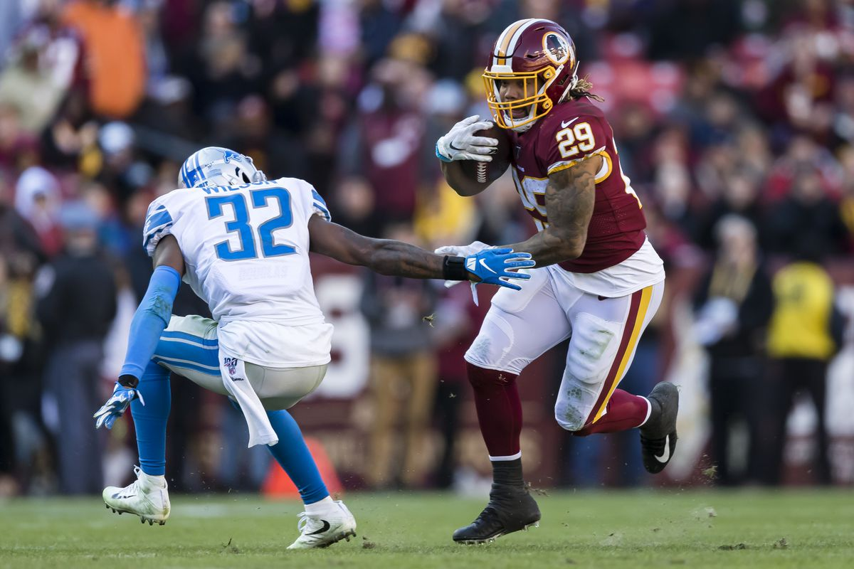 Washington running back Derrius Guice carries the ball as Tavon Wilson of the Detroit Lions defends during the first half at FedExField on November 24, 2019 in Landover, Maryland.