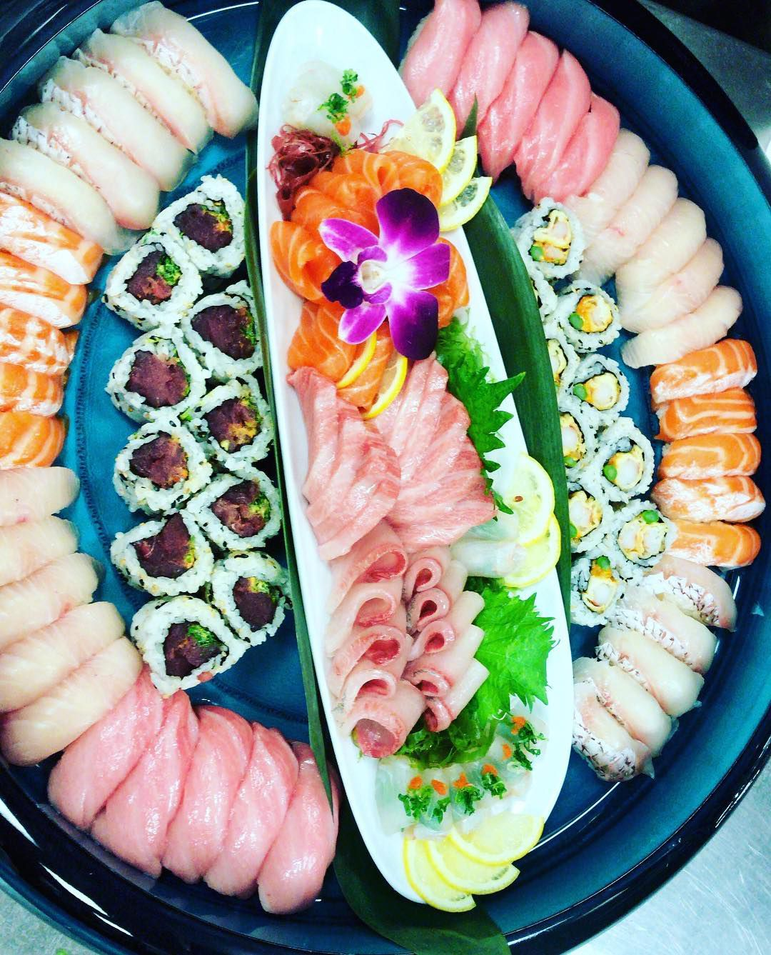 A round plate with sushi and sashimi