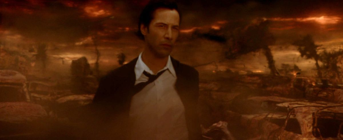 Constantine walks through an ashen, orange apocalyptic wasteland that might be hell