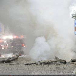 Steam rises after a steam pipe explosion on Tuesday, June 20, 2017, in Baltimore, Md. The underground steam pipe explosion rocked downtown Baltimore Tuesday afternoon, buckling the street, shattering windows on cars and buildings, and gushing a steam plume several stories high for more than an hour.