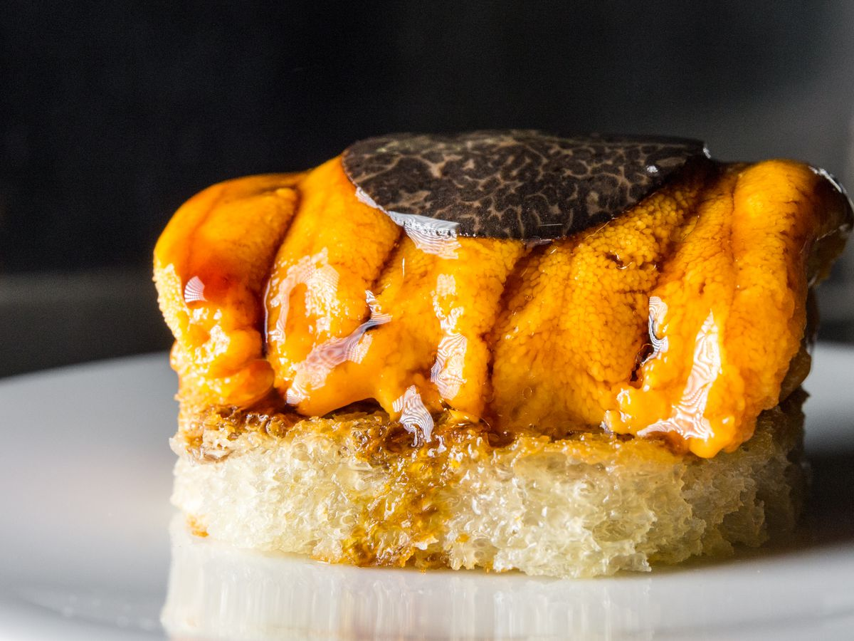 A slice of black truffle lays atop bright orange uni, which in turn sits above a slice of toast