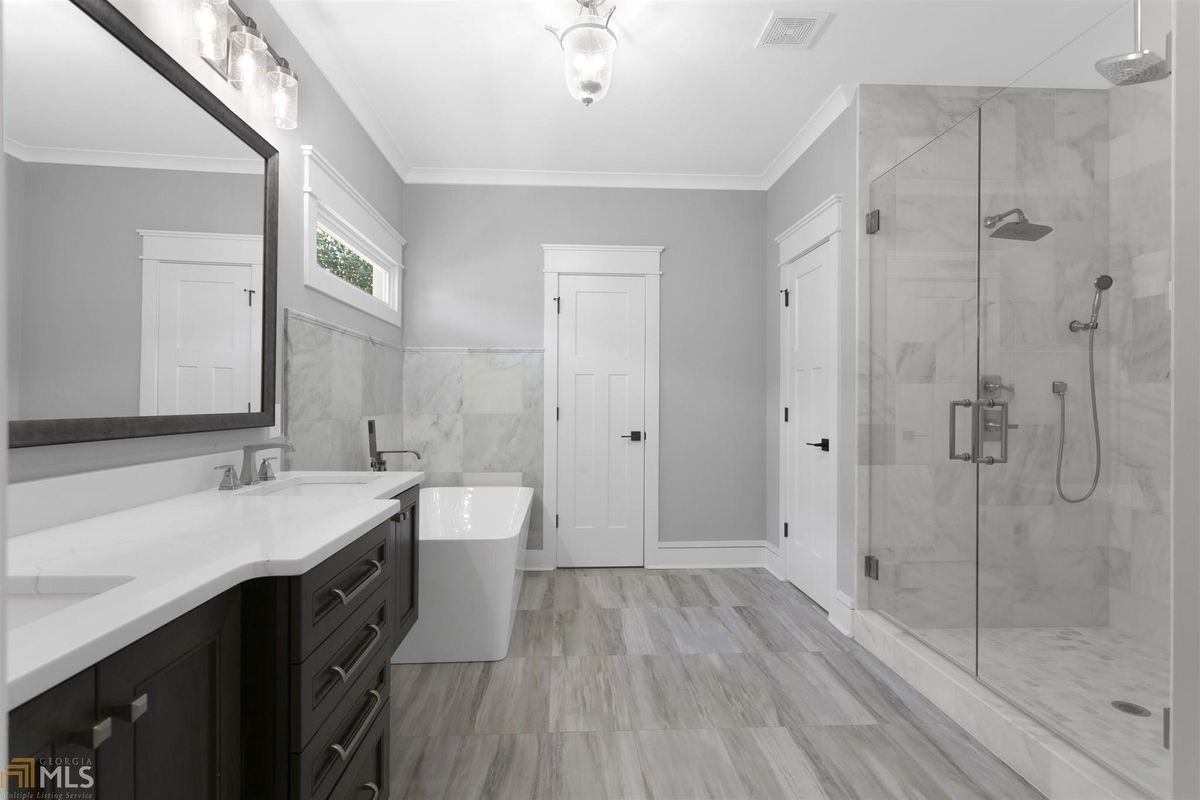 A gray master bathroom with a large shower at right.