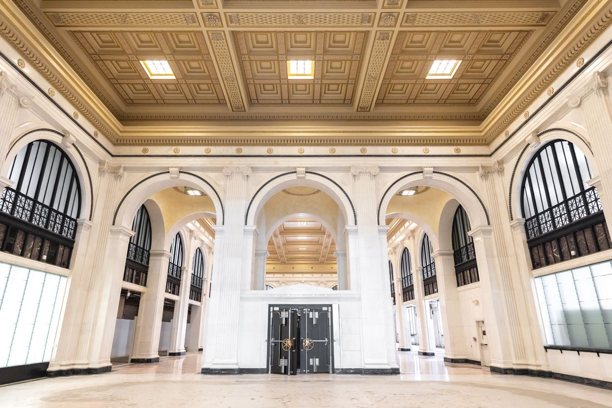 A room with white floors and gold coffered ceilings. Three arches lead to a large space with a bank vault in between.