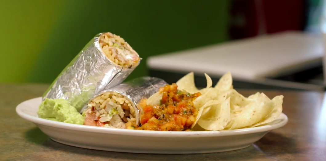A burrito, sliced in half and wrapped in foil, sits on a white plate with guacamole, salsa, and tortilla chips.