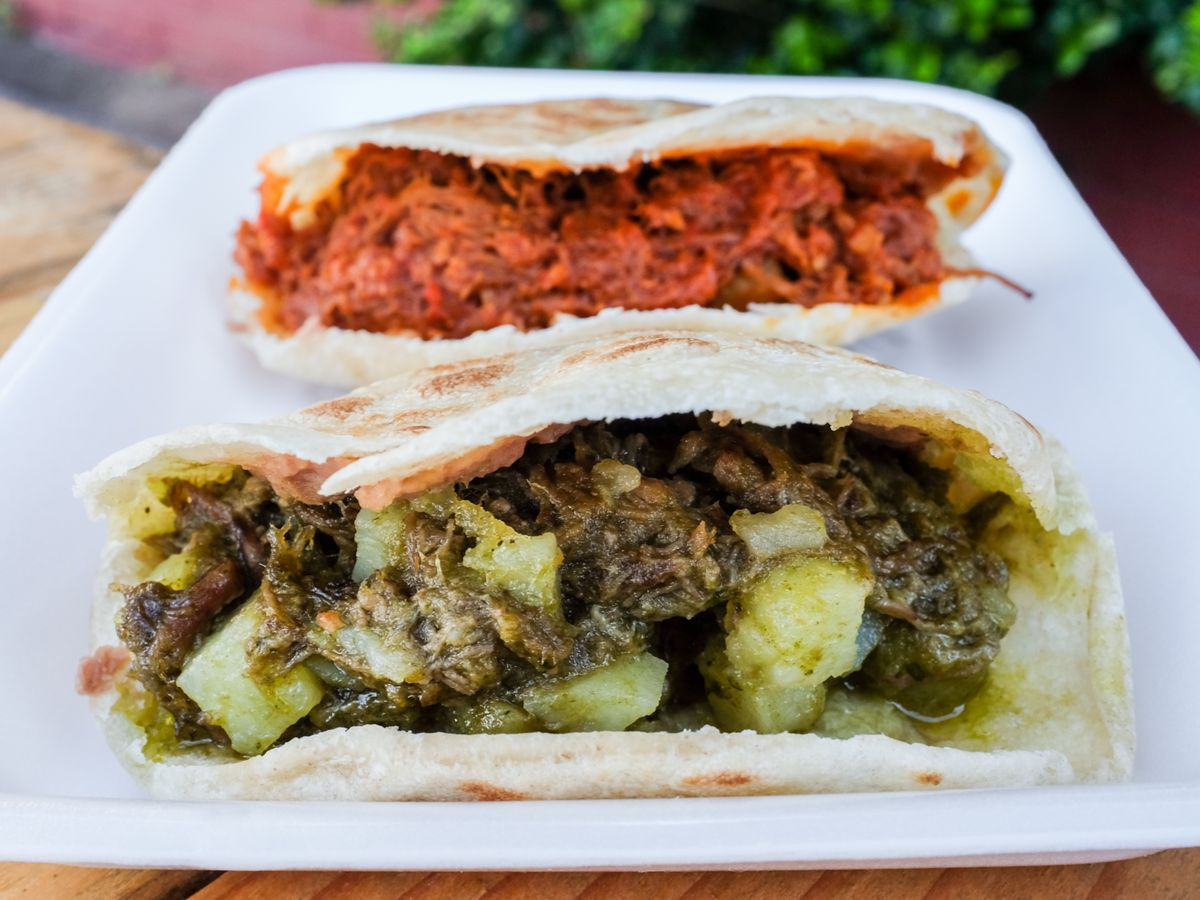 A gordita stuffed with bright red meat and another stuffed with green salsa verde meat and a white rectangular plate.