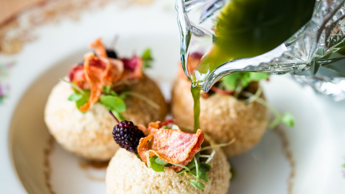 """A dish of pani puri made with potato masala and Camellia red beans stuffed into a puffy wheat ball """"puri"""" and filled with a fiery mint water """"pani"""""""