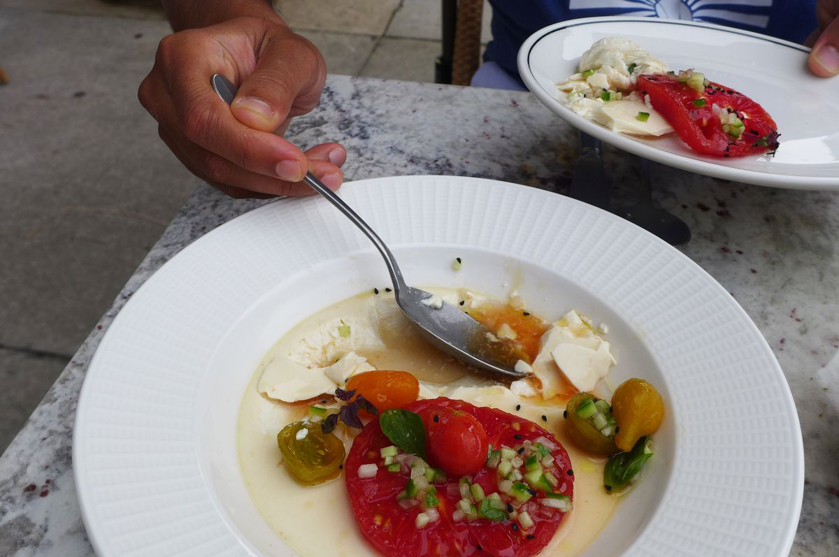 A hand holds a spoon lifting up tofu and colorful tomatoes in several hues.