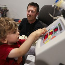 """Zach Thomas watches as his son Jackson, 3, presses the start button on his dialysis machine to start the treatment at his home in Kamas on Sunday, Sept. 8, 2019. """"He likes pressing buttons,"""" says Zach. He and his wife have tried to keep Jackson involved with the process as much as they can at his young age, explaining the basics of the condition and what the machine does."""