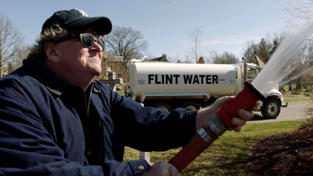Michael Moore in Fahrenheit 11/9 spraying a hose in front of a Flint Water truck