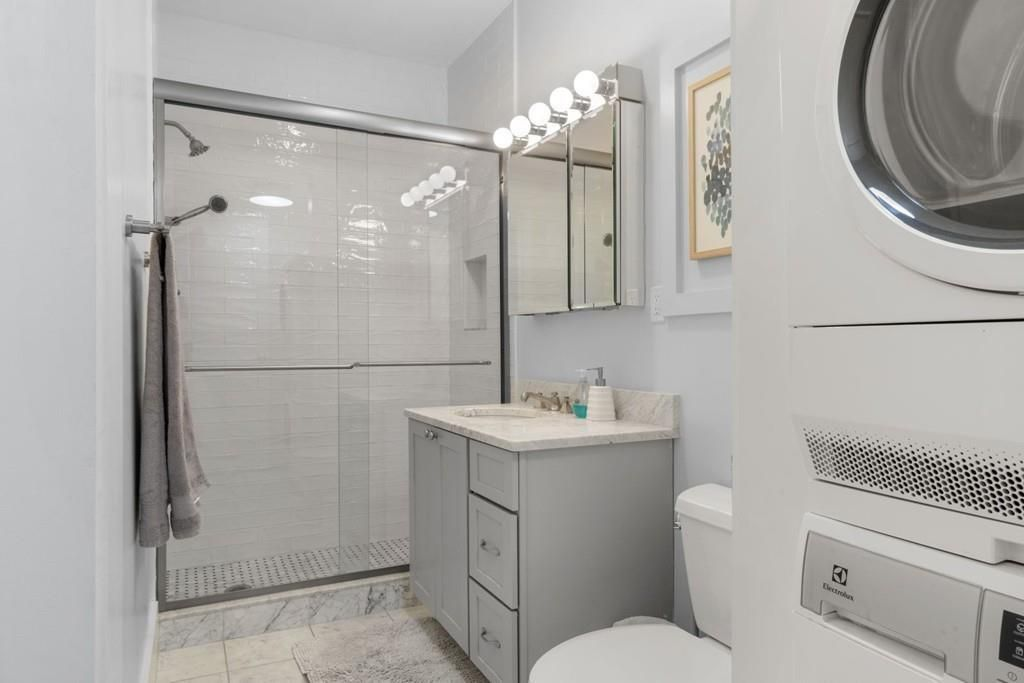 A bathroom with a glass-enclosed shower and a stacked washer-dryer.