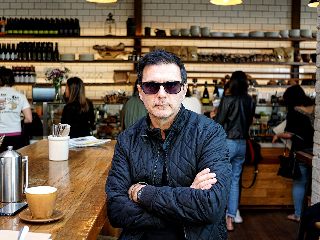 Chef Christophe Eme wearing sunglasses and posing with crossed arms at a restaurant in Los Angeles