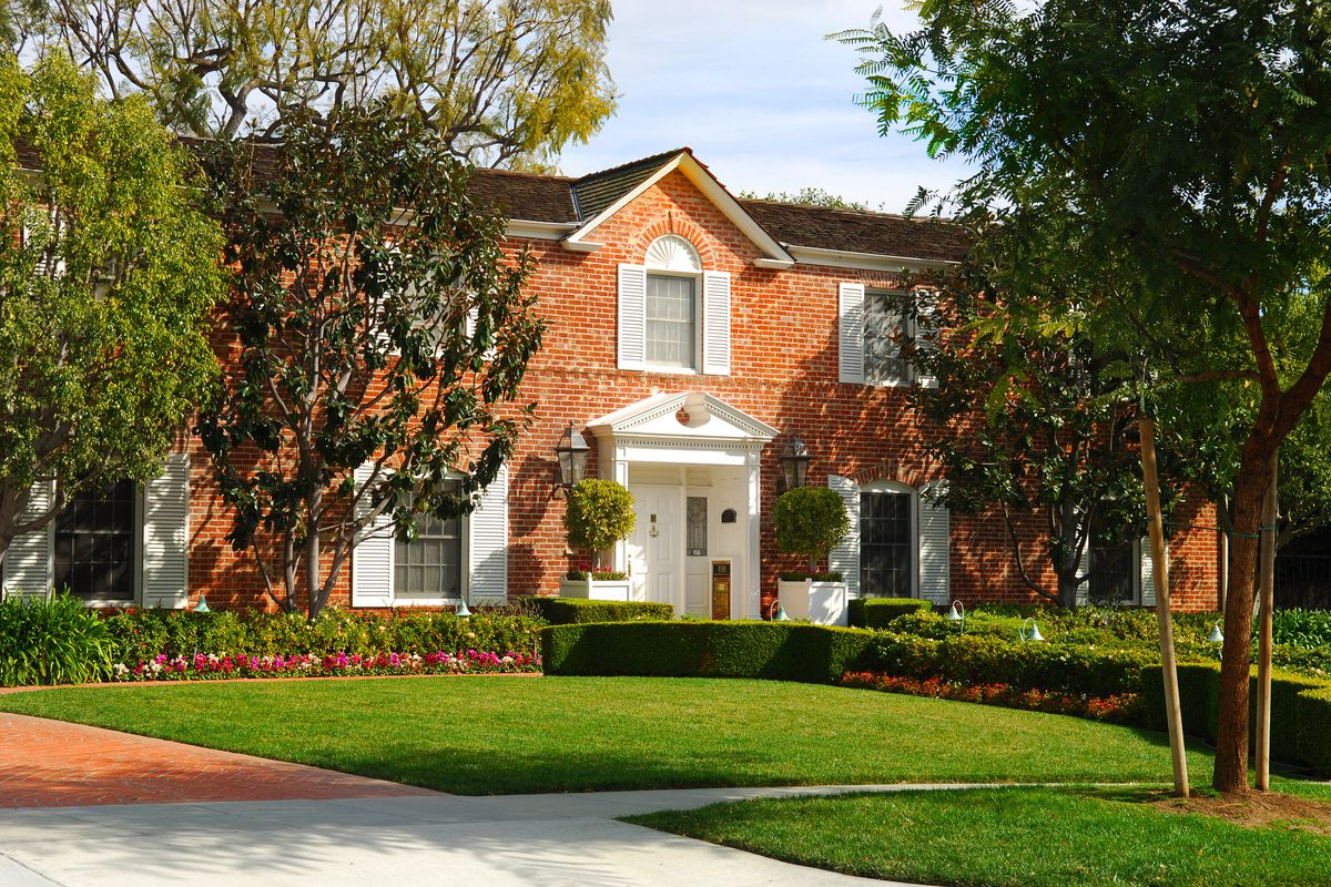 A traditional brick home with white front door and large green yard.