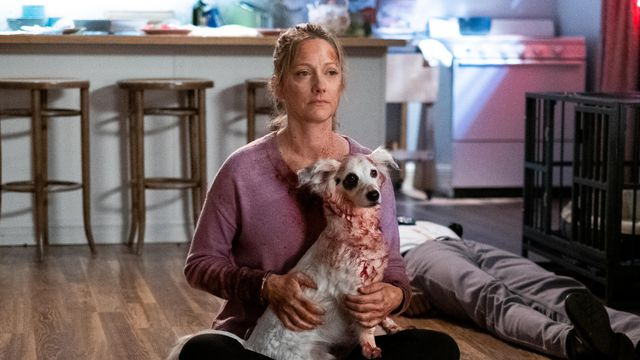 Maggie (Judy Greer) sits on the floor holding Reuben (Chico the dog)