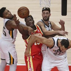 Atlanta Hawks center Clint Capela is triple-teamed by Utah Jazz defenders Donovan Mitchell, Rudy Gobert and Georges Niang, from left, while reaching for a rebound during an NBA basketball game Thursday, Feb 4, 2021, in Atlanta.