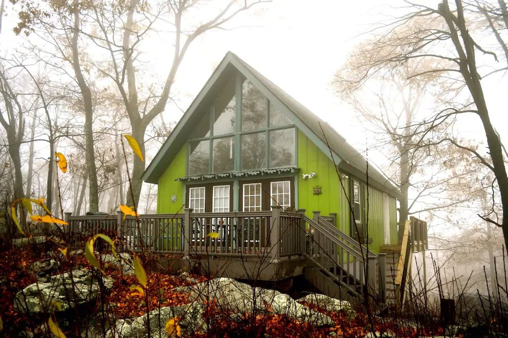A green, A-frame cabin in the middle of the woods of Great Cacapon, West Virginia.