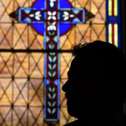 The Rev. Salvatore Sapienza is silhouetted by the stained glass inside the Douglas Congregational United Church of Christ in the village of Douglas, Mich., on Tuesday Oct. 13, 2020. As part of the Our Faith Our Vote 2020 initiative, volunteers at the church will drive voters with their completed mail-in ballots to the county clerk's office to drop them off in person. The drivers and voters will be masked and separated in vehicles to minimize any COVID-19 risk.