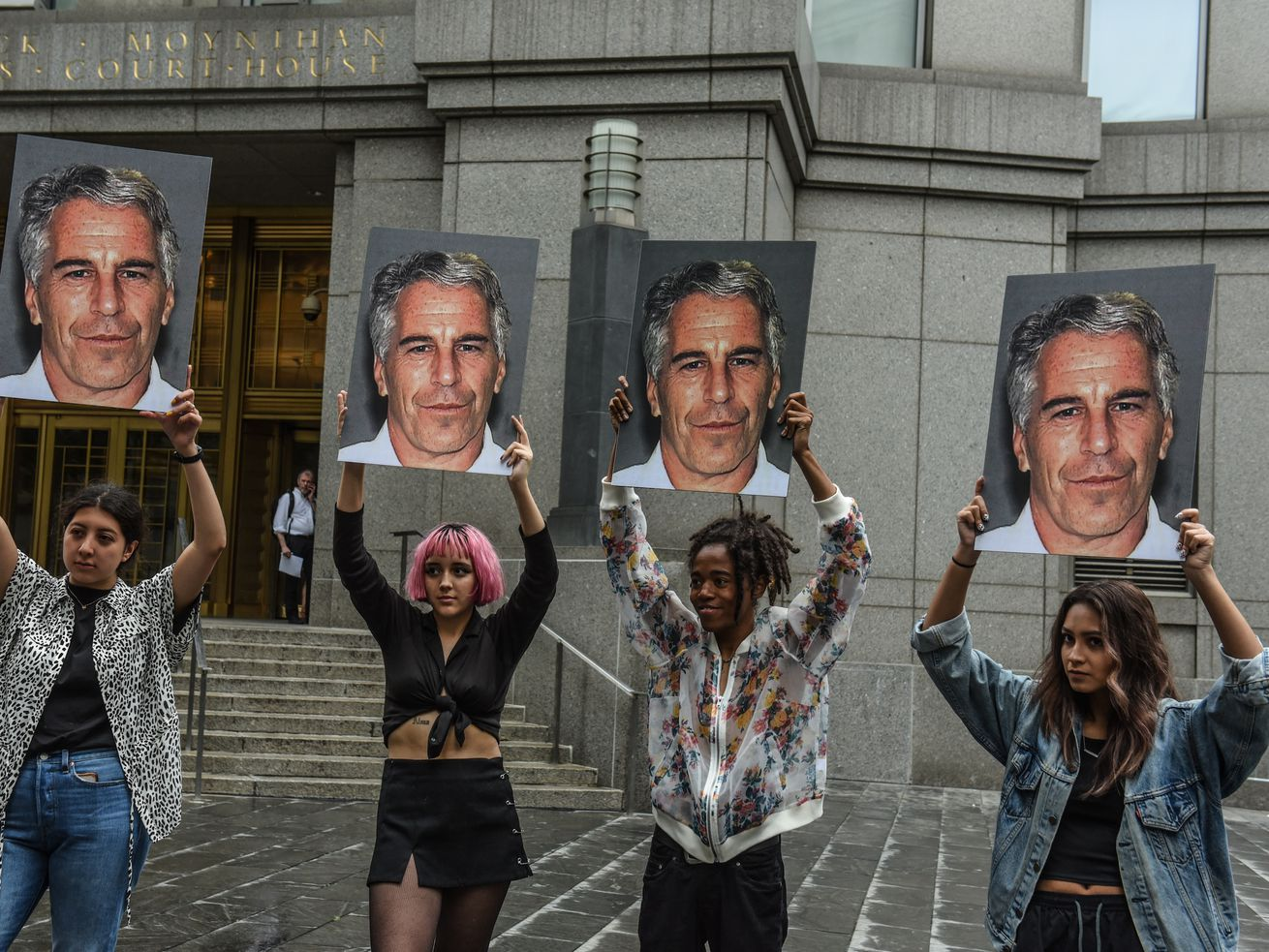 Protesters hold up signs with photos of Jeffrey Epstein in front of a New York City federal courthouse on July 8, 2019