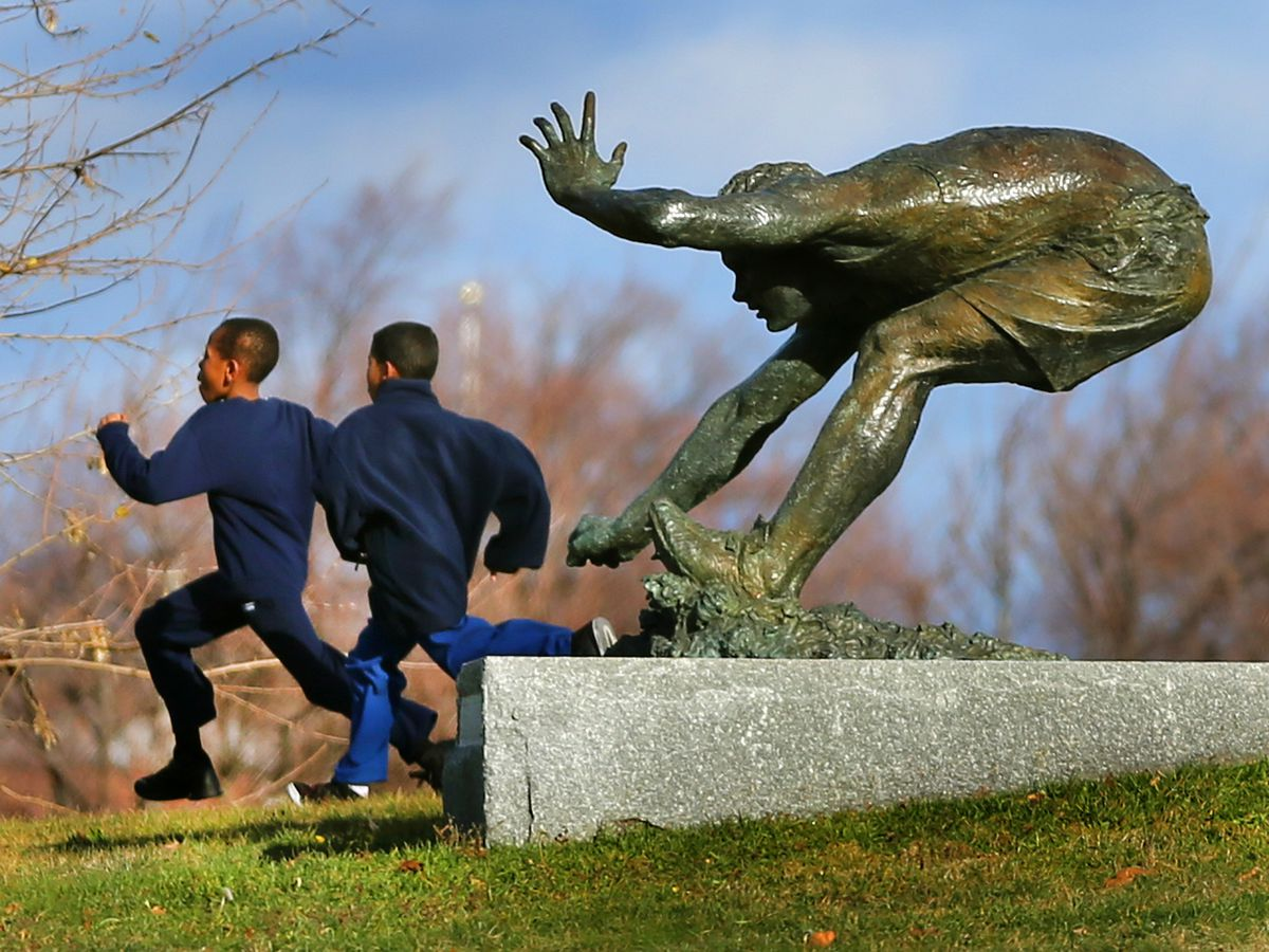 Bronze statue of a crouching man at the end of a long jump, and there's two kids running by the statue.