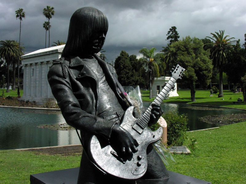 A monument statue at the Hollywood Forever cemetery. The statue is of Johnny Ramone who is dressed in a leather jacket and jeans. He is playing a metallic silver guitar.