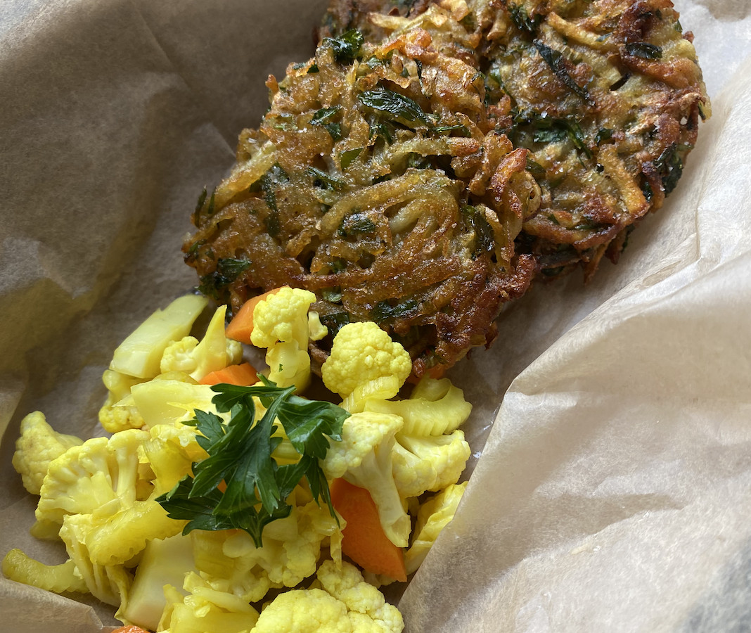 A fried potato pancake and scoop of turmeric-pickled vegetables placed inside a takeout container