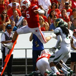 Quarterback Tanner McEvoy hurdles his own teammate to avoid the defense.