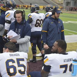 Luke Doerger and Yazeed Atariwa take instruction from an assistant coach on the sideline.
