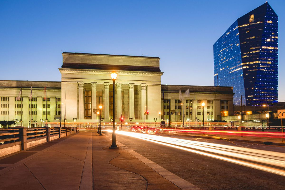 The exterior of 30th Street Station in Philadelphia. There is a street in the foreground. In the background is the station which has a flat roof and columns flanking the entryway.