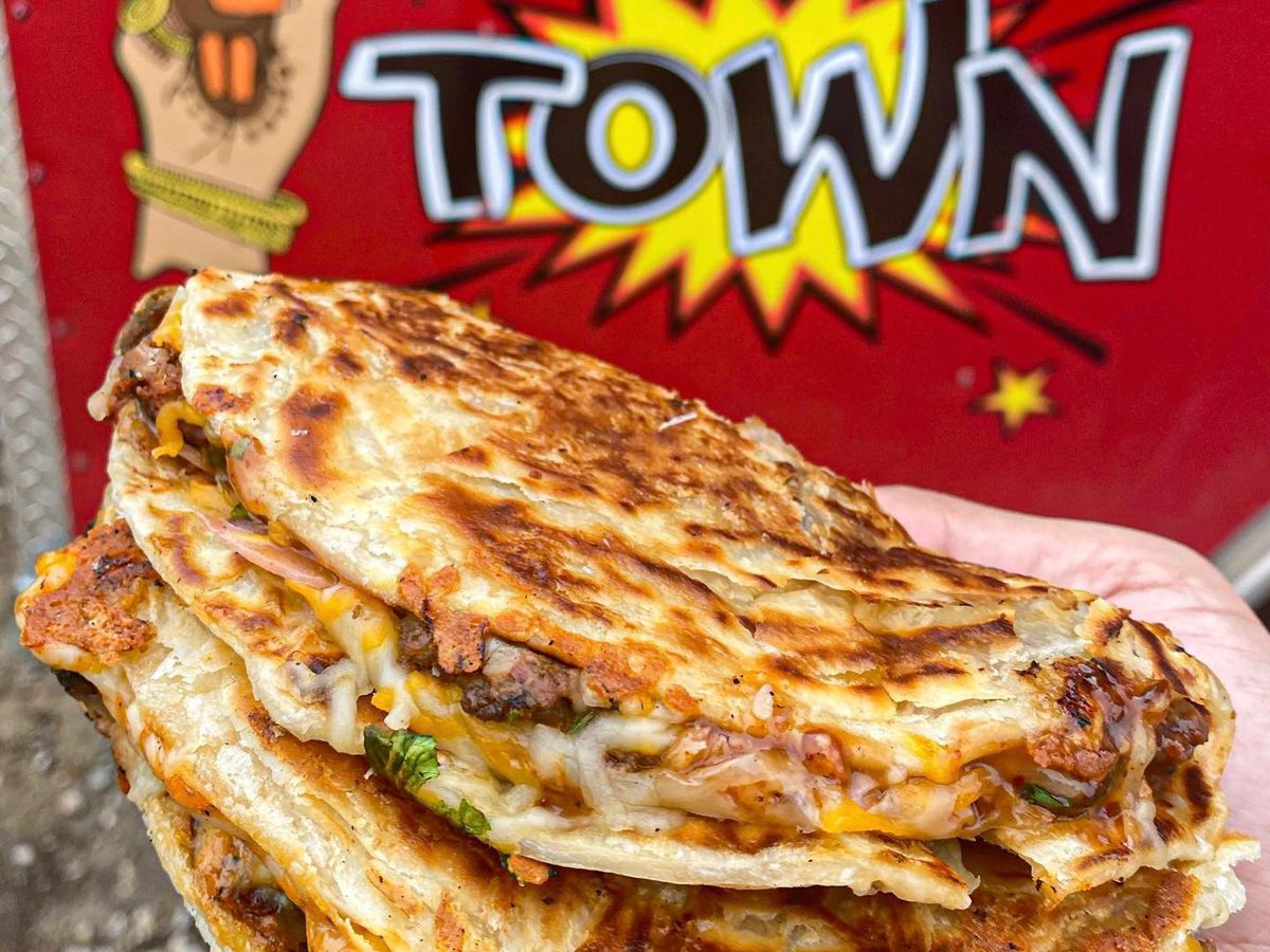"""a hang holding two cheesy paratha quesadillas in front of a red food truck. On the food truck is a cartoon of a mendhi hand and the word """"town"""" in big letters"""
