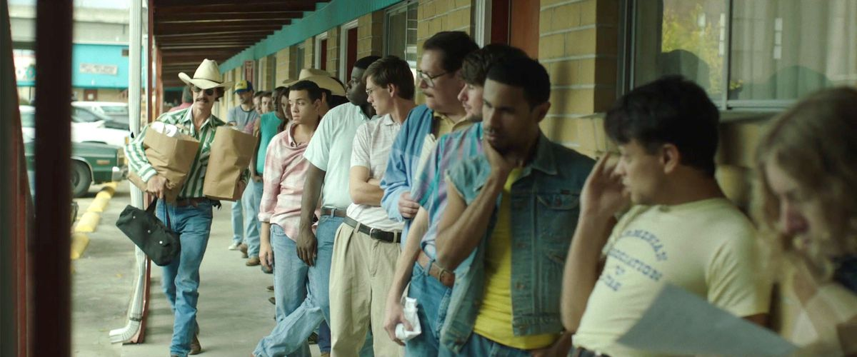 Matthew McConaughey as Ron Woodroof in Dallas Buyers Club carries a couple of brown paper grocery bags past a line of waiting men outside a seedy motel