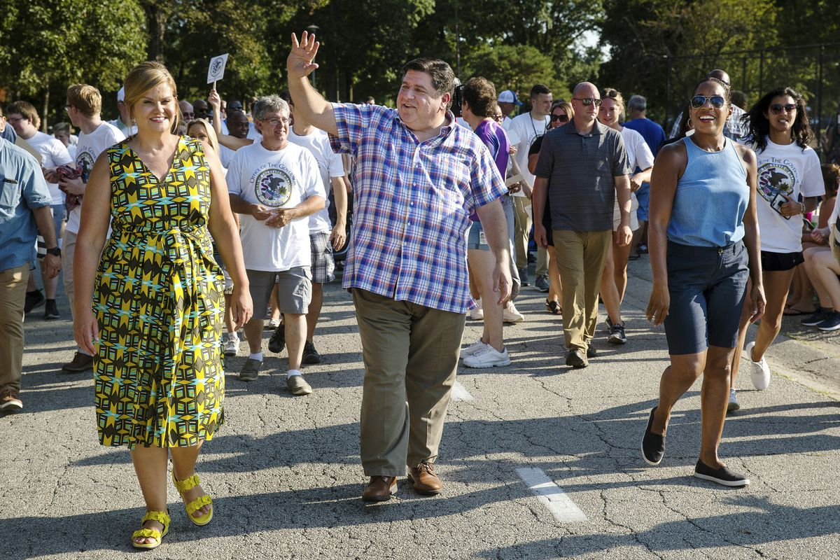 Gov. J.B. Pritzker waves while walking in the Illinois State Fair's Twilight Parade in Springfield in 2019.