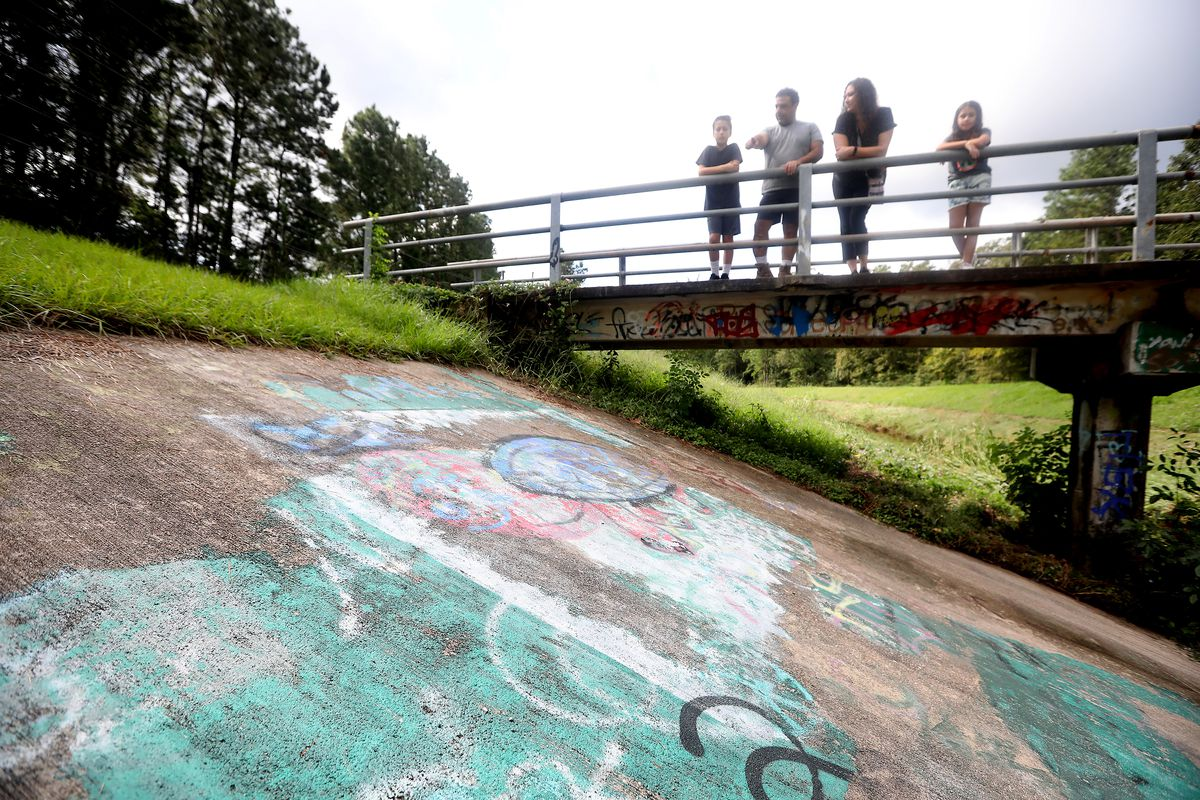 Mohammed Ghanayem, second from left, points to an area with graffiti as son, Nishan Ghanayem, 12, left, wife Layla Kaiksow and daughter Zayna Ghanayem, 9, look on along a walking path in Kingwood, Texas, on Sunday, Oct. 3, 2021. Mohammed and Layla take their kids to school using the same path and have found, on several occasions, racist graffiti. The green paint shows areas that have been painted over.