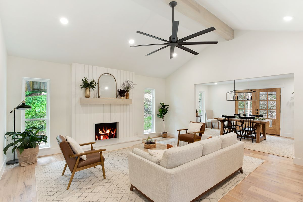 An open concept living and dining room features vaulted ceilings and a fireplace surrounded by shiplap.