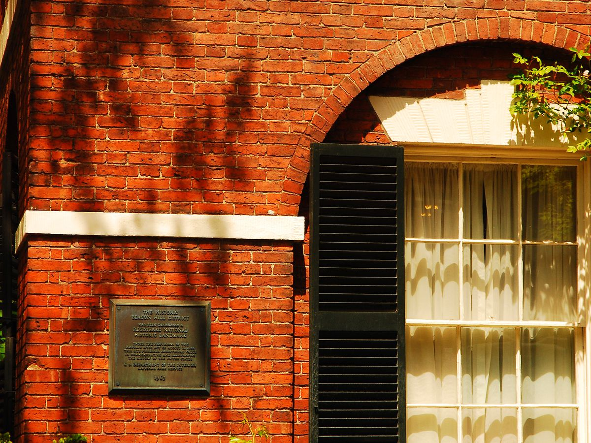 A closeup of a brick building with one window showing.